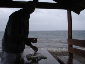 Jeg spiser brød og omul i regnet på stranden ved Bajkal (Listvjanka)