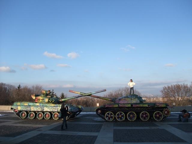 To jenter leker seg ved de to farvelagte tanksene som er stilt opp utenfor krigsmuseet i Kiev.
