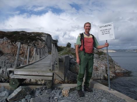 Her står jeg ved det pussige skiltet om at ferdsel over broen skjer på eget ansvar.