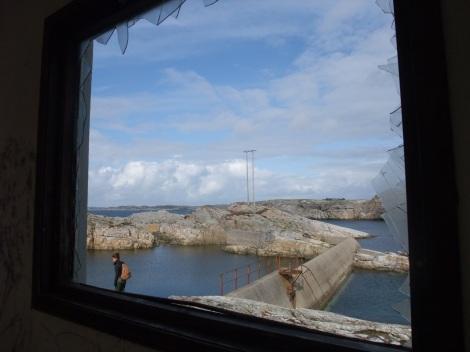 Gjennom et knust vindu i det lille betonghuset ser vi demningen i det som egentlig var vannforsyningen i bølgekraftverket.